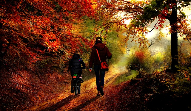 mother biking with daughter in the autumn